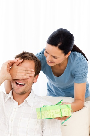 paquet: Happy woman giving a present to his boyfriend while hiding his eyes