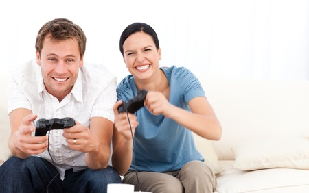 Excited woman playing video games with her boyfriend on the sofa Stock Photo - 10170386