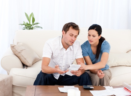 Man showing a bill to his girlfriend sitting on the sofa photo