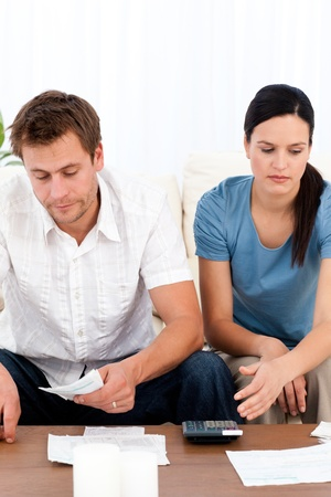 Desperate couple looking at their bills sitting on the sofa photo
