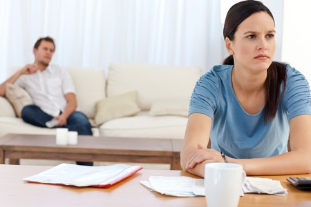 Angry woman doing her account while her boyfriend relaxing Stock Photo - 10172562