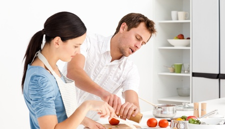 stiring: Man putting salt and pepper while his girlfriend stiring the sauce Stock Photo