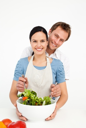 Happy man mixing a salad with his girlfriend in the kitchen photo