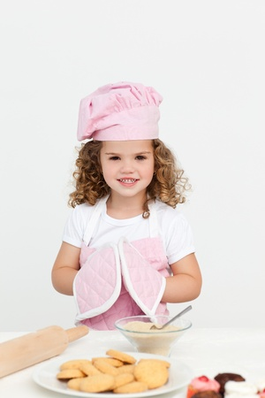 Cute girl with kitchen gloves while preparing cookies photo