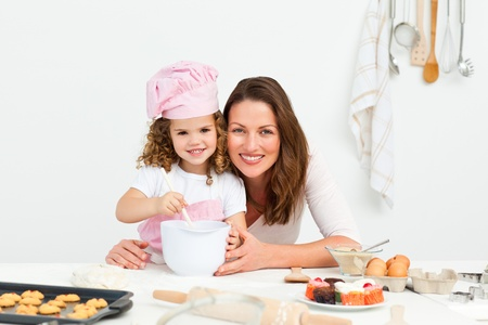 mother cooking: Portrait of an adorable mother and daughter preparing a daugh together