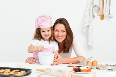 children cooking: Retrato de una adorable madre e hija preparando una hija juntos