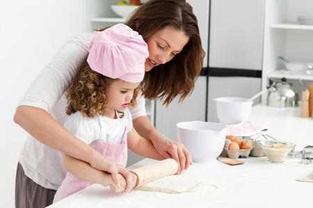 kitchen apron: Mother and daughter using a rolling pin together Stock Photo