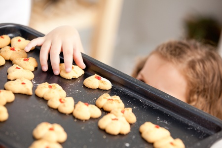 Close up of a little girl taking a cookie behind her mother photo