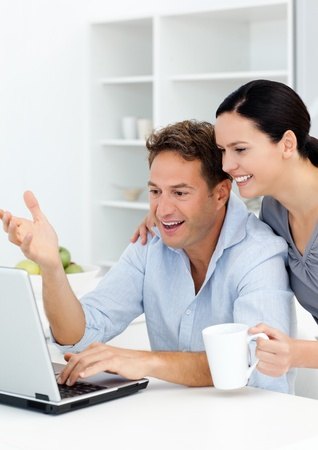 finding love: Lovely couple laughing while watching something on the laptop screen