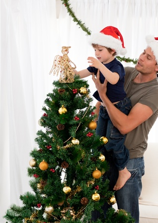 Cute son decorating the christmas tree with his father photo