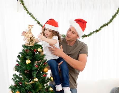 Cute daughter decorating the christmas tree with his father photo