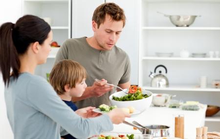familia comiendo: Pap� sirviendo ensalada a su familia para comer