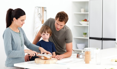 Lovely woman cutting bread for her son ad husband  photo