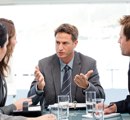 Severe manager talking to his team at a table photo