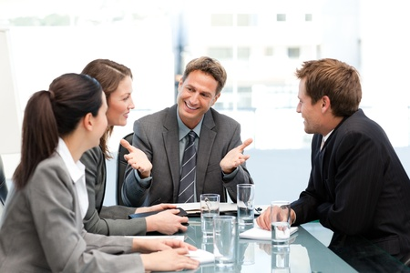 delighted: Delighted managertalking to his team at a table Stock Photo