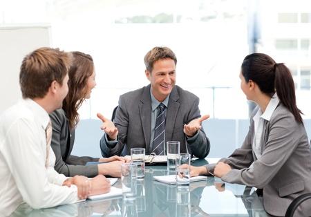Cheeful manager in gesprek met zijn team op een vergadering