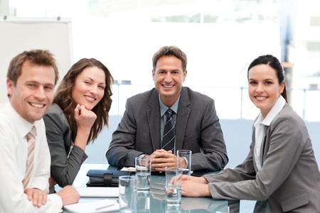 Portr�t eines positiven Teams, die an einem Tisch Stockfoto