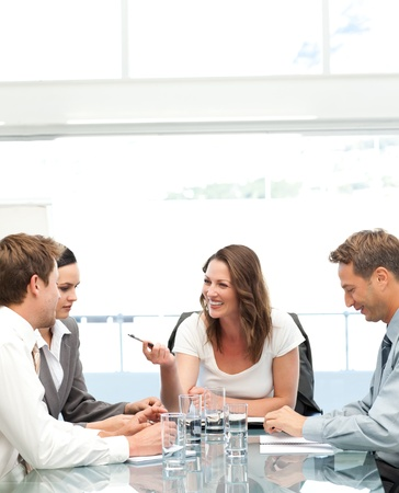 Cheerful manager talking to her team during a meeting photo