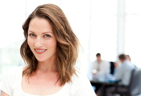 Relaxed businesswoman standing in front of her team while working photo