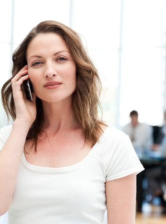 Confident businesswoman on the phone while her team is working photo