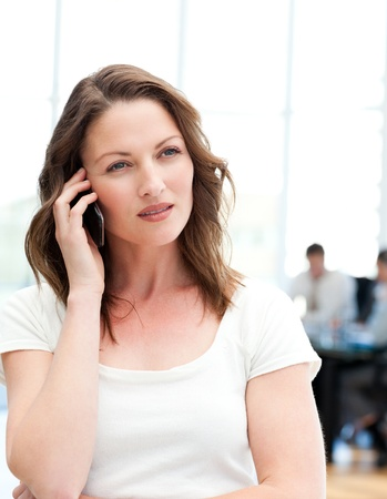 conference call: Pensive businesswoman on the phone while her team is working