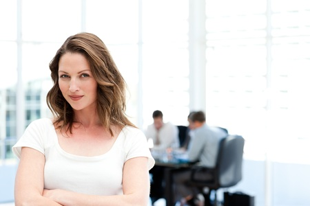 Beautiful businesswoman standing in front of her team while working  photo