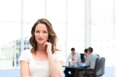 Pensive businesswoman standing in front of her team while working photo