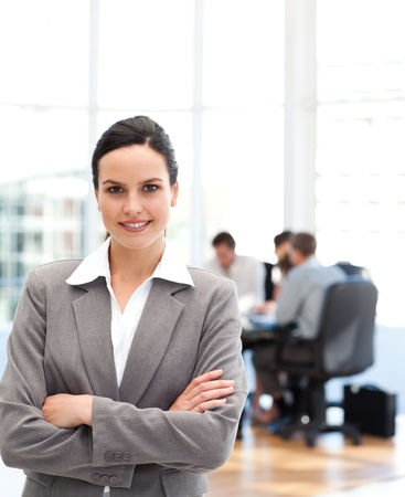 Cheerful businesswoman standing in front of her team while working photo