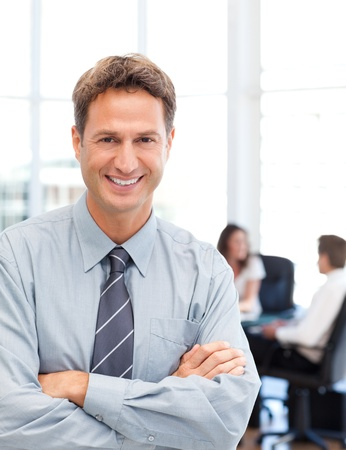 executives: Happy businessman standing in front of his team while working at a table