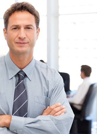 Assertive businessman standing in front of his team while working at a table photo