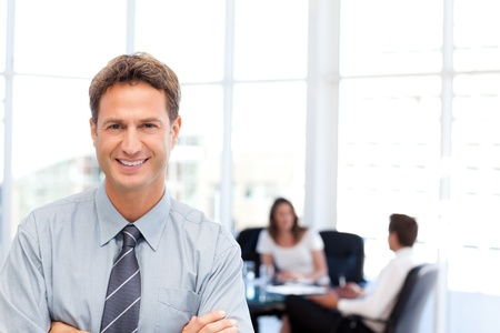 Proud businessman posing in front of his team while working photo