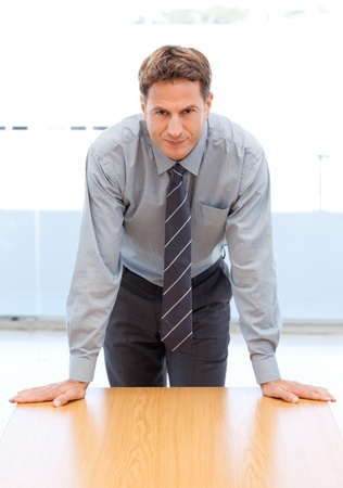 Confident businessman posing leaning on a table photo
