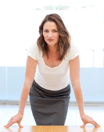 assertive: Confident businesswoman posing leaning on a table
