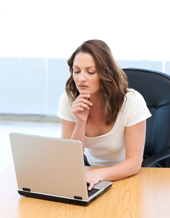 Pensive businesswoman working on laptop at a table photo