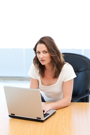 Portrait of a businesswoman working on laptop at a table photo
