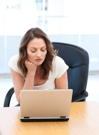 Thoughtful businesswoman working on laptop at a table photo