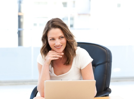 Happy businesswoman working on laptop at a table photo
