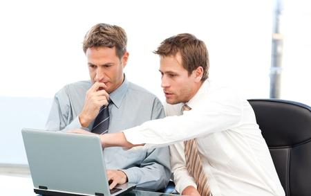 Zwei gut aussehend Gesch�ftsleute arbeiten zusammen an einem Projekt, die an einem Tisch Stockfoto