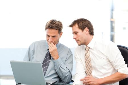 work together: Twee geconcentreerde ondernemers samen op een laptop werken