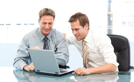 Two happy businessmen working together on a laptop sitting at a table photo