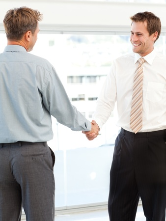 concluding: Two happy businessmen concluding a deal by shaking their hands
