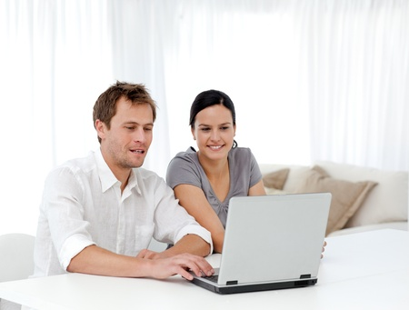 Happy man and woman looking at something on the laptop photo