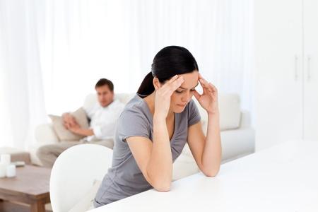 preocupacion: Mujer cansada tener un dolor de cabeza sentado en una mesa en la sala de lliving