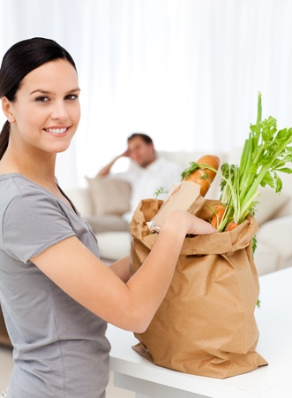 Happy woman with bags in the kitchen after shopping photo