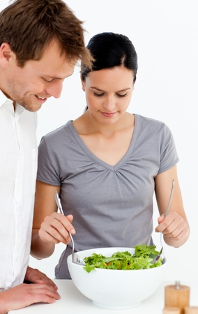 Cute couple preparing a salad together photo