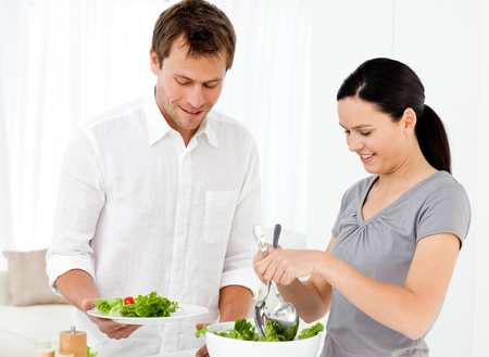 Happy woman serving salad to his boyfriend for the lunch photo