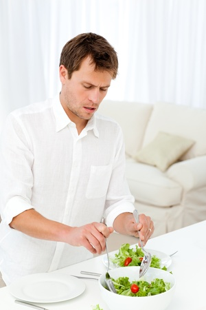 Single man serving salad standing at a table photo