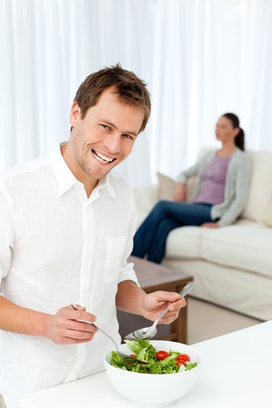 Happy man preparing lunch while his girlfriend relaxing photo