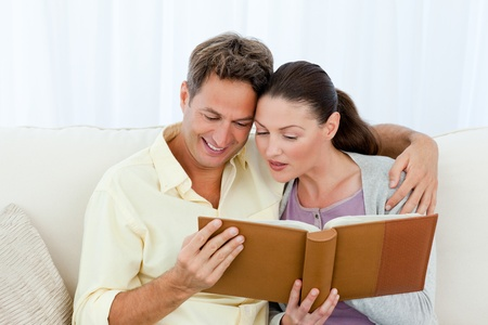 Attentive man and woman looking at a photo album on the sofa Stock Photo - 10173027