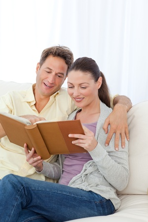 Cute couple looking at a photo album on the sofa Stock Photo - 10172931